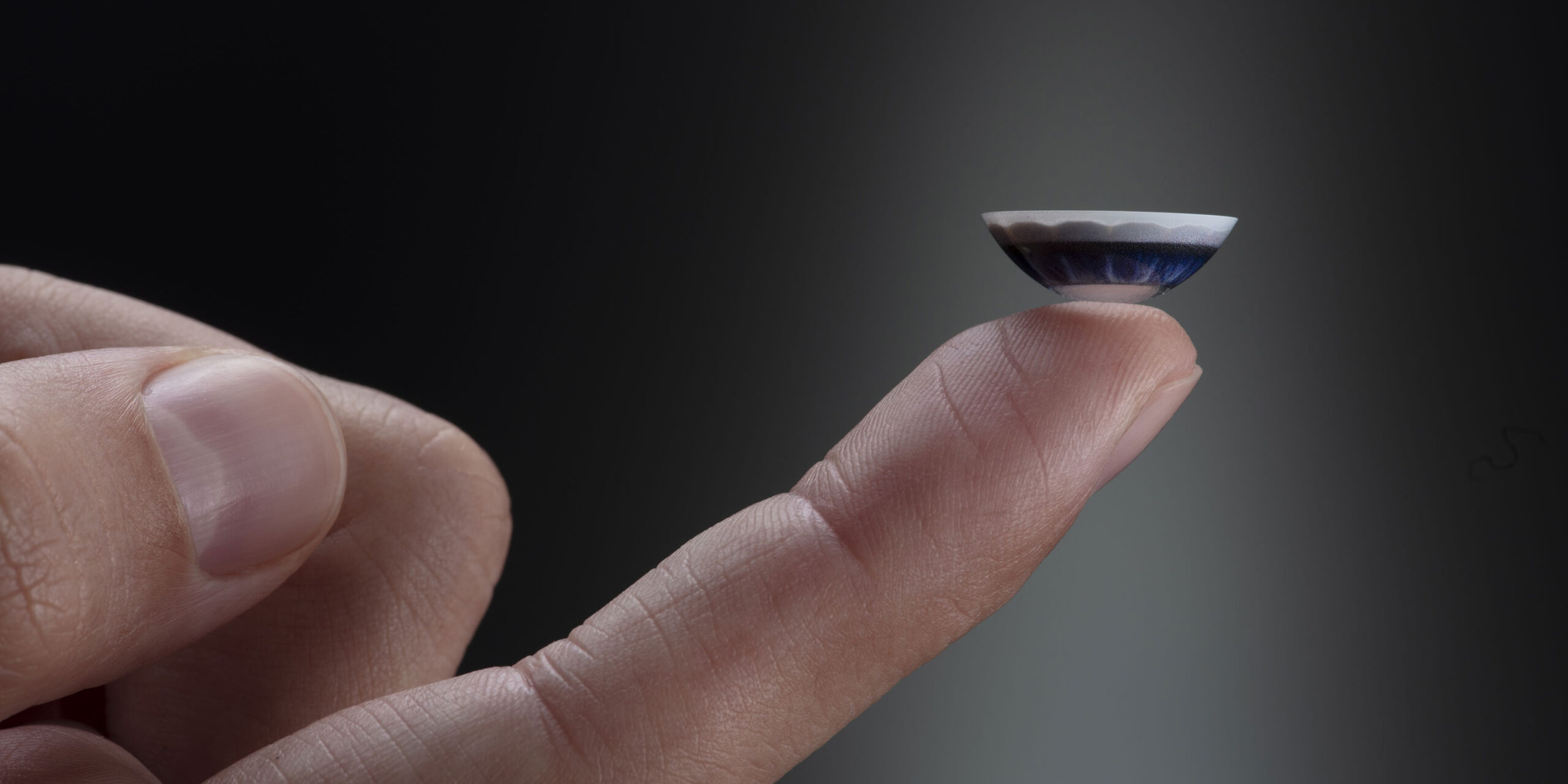 MojoLens smart contact lens balancing on a finger